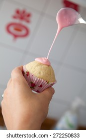 woman glazing a pink muffin
