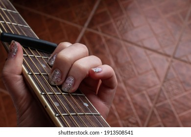 A woman with glitter nail polish plays an A minor chord on an accoustic guitar, fitted with a capo, February 2021 during COVID-19 lockdowns.