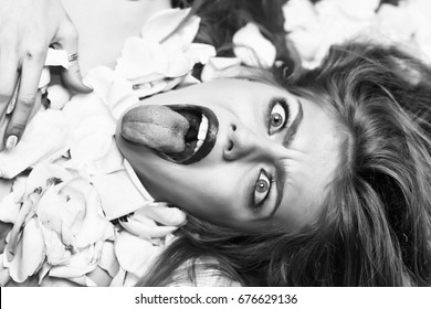 woman with gloss and silk hair looking forward. crazy face lying in flower petals of rose, beauty and fashion, retro old vintage black and white style