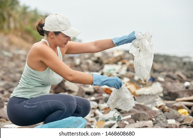 Woman in gloves collects plastic trash on the background of the coast.