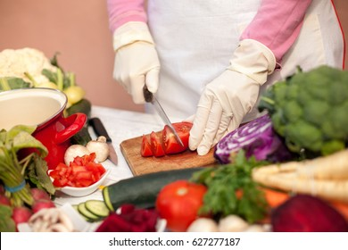 Woman with gloves cutting tomato on cutting board