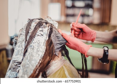 Woman in gloves is dying hair. hair dyeing. Hair in foil