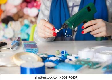 Woman glues glue gun. Woman doing kanzashi of satin ribbons. Women's handicrafts. Kanzashi ribbons. The concept of creativity.