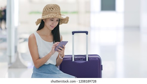 Woman go travel and wait in the airport with cellphone