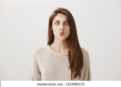 Woman goes crazy from boredom. Portrait of funny childish european girl making faces, squinting and puckering lips, trying to look at her nose, standing against gray background