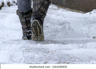 A woman goes down a staircase in winter. In winter there is a danger of slipping on a snow-covered staircase.