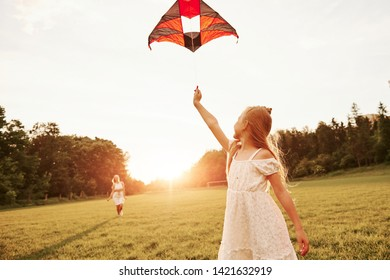 Woman is going to the child. Mother and daughter have fun with kite in the field. Beautiful nature.