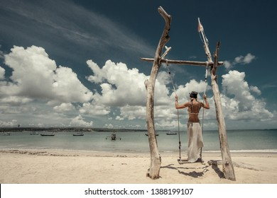 Woman going on the hanging swing on the sea on the beach