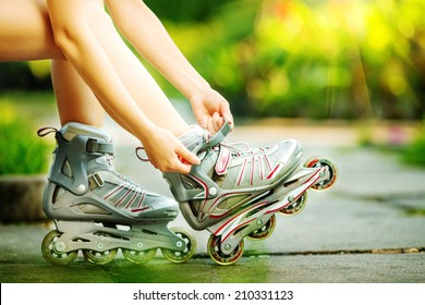 Woman is going rollerblading. Sitting on a bench in a park and putting on inline skates. Close up. Sport lifestyle.