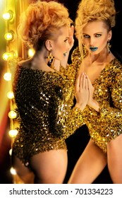 Woman in gold bodysuit posing on mirror background