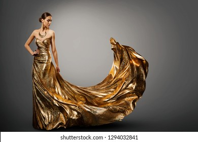 Woman Gold Dress, Fashion Model in Long Waving Fluttering Gown, Young Girl Beauty Studio Portrait