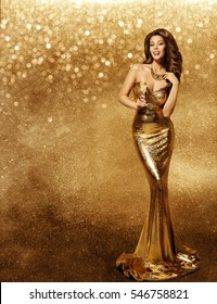 Woman Gold Dress, Fashion Model with Champagne in Long Golden Gown, Girl Celebrating Holiday over Sparkles background