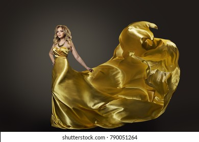 Woman Gold Dress, Fashion Model Dancing in Long Artistic Evening Silk Gown, Waving Fly Fabric