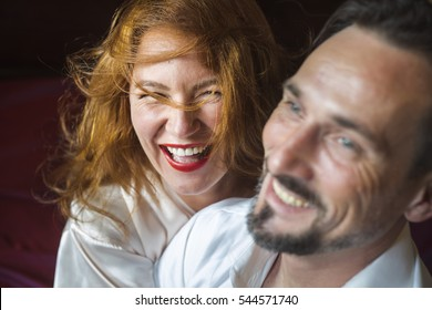 Woman with gold hair, laughs with her man. Happy together . Woman and man having fun time together, indoor. Couple in bedroom