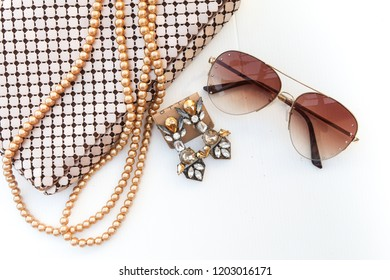 Woman golden accessory fashion set / gem earrings ,fashion sunglasses ,metallic gold evening bag and pearl necklace  on white background