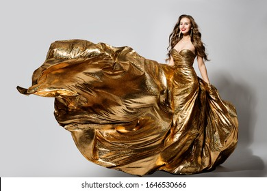 Woman in Golden Dress Flying on Wind, Happy Beautiful Lady in Fluttering Sparkling Gold Gown