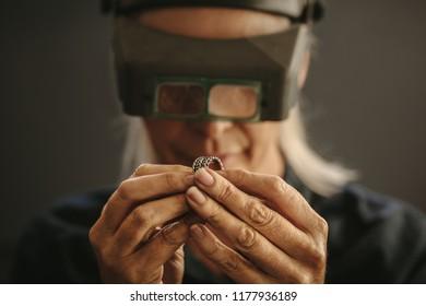 Woman goldsmith examining sliver designer ring using magnifying glass. Professional jeweler inspecting a ring using magnifying glass.