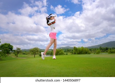 woman golf player in action being setup address after hit the golf ball away from fairway to the destination green off, fairway at day light sky