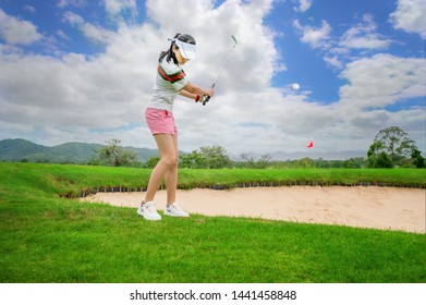 woman golf player in action being setup address after hit or chip a golf ball away from rough of fairway to the destination green at day light sky