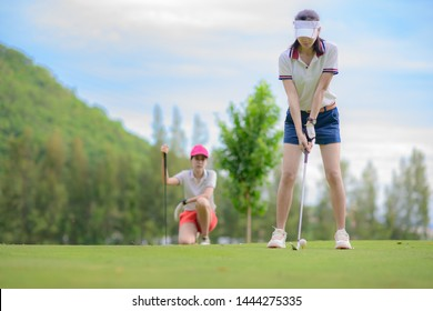 woman golf player in action being setup address to back swing for hit the golf ball away from T-OFF to the destination on the green, fairway at day light sky, PAR 3 T OFF
