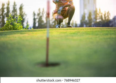 a woman golf player in calculate line measurement going to have putter on the green of golf course for a best resulted