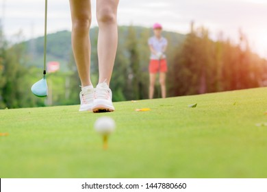 woman golf player in checking line to hit the ball to fairway, walking to hit the golf ball after line checking target, opponent competitor or golf buddy watching in background