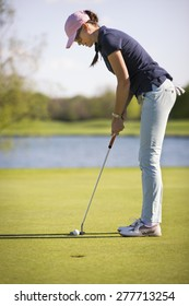 Woman golf player concentrating for putting on green, with lake in background.
