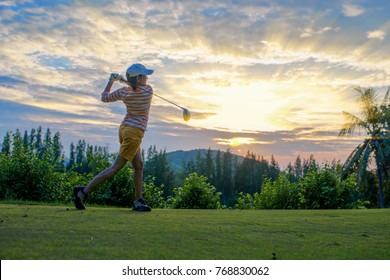 woman golf player at the end og action after hit the golf ball away from tee off in the golf course to fairway ahead, with sunset scenery in back ground