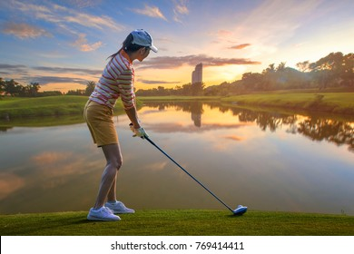 woman golf player prepare standing address on the tee off in golf course, ready to hit the ball away fly over the lake to the fairway ahead