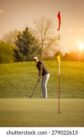 Woman golf player putting on green looking at flag, with sunset in background.