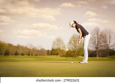 Woman golf player putting on green at dusk, with empty copyspace.