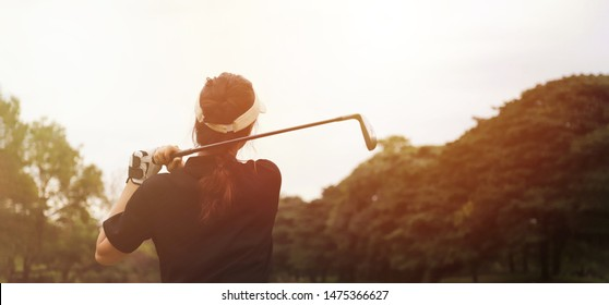 Woman golf player swing shot on course in the park with warm sunlight, leisure or sport concept, website banner template style with copy space