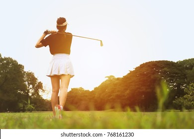 Woman golf player swing shot on course in the park with warm sunlight, leisure or sport concept