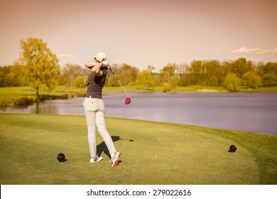 Woman golf player swinging golf club from tee box at dusk.