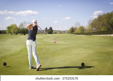 Woman golf player teeing off ball.