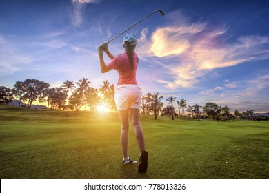 woman golf player at th end of downswing after hit a golf ball away from fairway to the green forward in a golf course