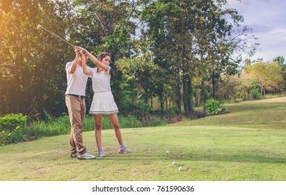 Woman golfer doing practice with assistance of her personal trainer at golf club