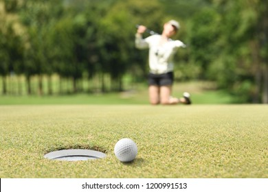 Woman golfer feeling disappointed after a putted golf ball missed the hole