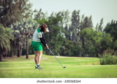 Woman golfer with a golf club on the tee box