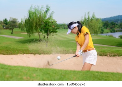 woman golfer hit sand ground exposure trying to approach or reach to hole final destination on the green, hit sand bunker attempt by woman golfer