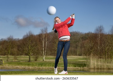 Woman golfer hitting the golf ball with a driver in front of a water hazard on a golf course with the ball flying through the air towards the camera
