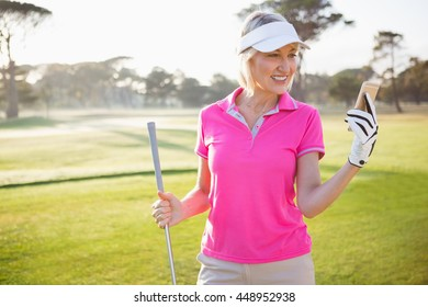 Woman golfer looking her mobile phone on field