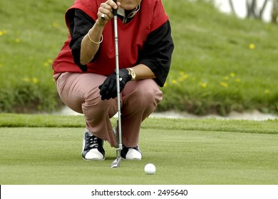 The woman the golfer to prepare for impact of a ball