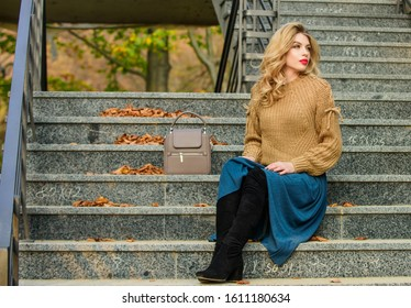 Woman with gorgeous hairstyle sit on stairs outdoors. Fall fashion trend. Layer oversize knit over girly skirt. Wearable trends. Fall outfit formula. How to Style Sweater and Skirt Combo for Fall.