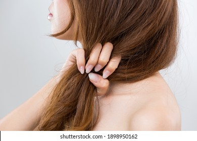 The woman is grabbing her damaged hair.