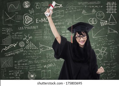 Woman in graduation gown expressing success in front of blackboard