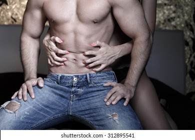 Woman grasps sexy macho mans abs at night