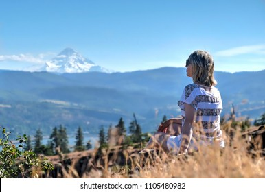 Woman in grass with view of Mount Hood. Columbia River Gorge. Catherine creek. Columbia River Gorge. The Dalles. Oregon. United States of Amrica.