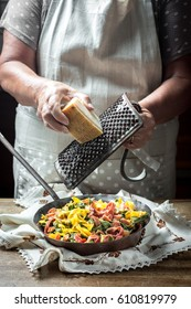 Woman grating cheese over cooked fresh homemade colored pasta. Vintage style frying pan and grater.
