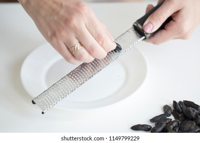 Woman grating tonka beans on kitchen table